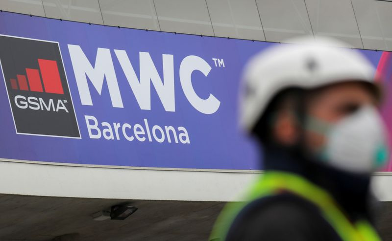 FILE PHOTO: Employee is pictured next to the logo of the cancelled event MWC20 (Mobile World