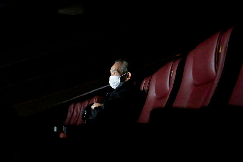 FILE PHOTO: A man wears a protective mask as he watches a movie, following the outbreak of the