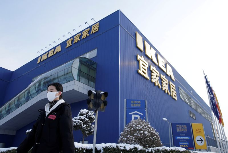 FILE PHOTO: Woman wearing a face mask walks past a closed IKEA store in Beijing