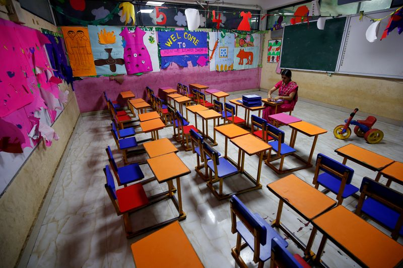FILE PHOTO: A teacher sits in an empty classroom after Tamil Nadu state government ordered the