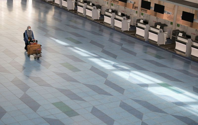 FILE PHOTO: A woman pushes a luggage cart near closed check-in counters at Haneda Airport in
