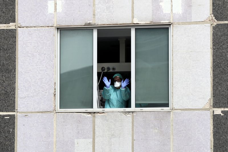 Medical staff in protective gear wave from the Intensive Care Unit of La Paz Hospital in Madrid