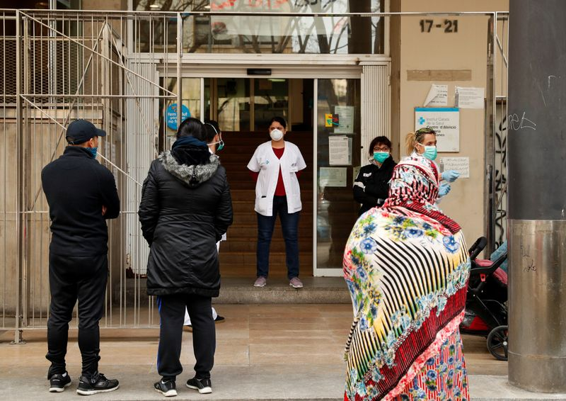 People stand in a queue to enter into a Medical Center, as medical staff check them, during an