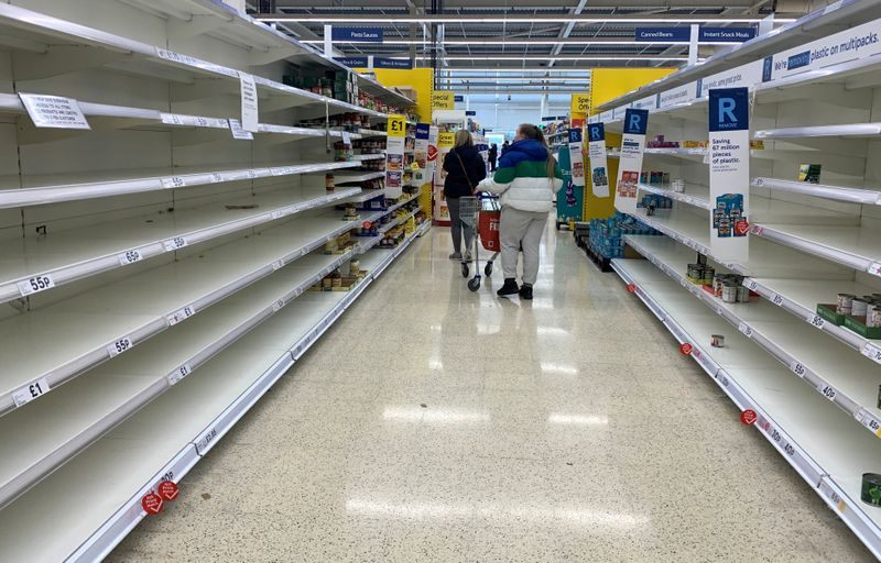 A customer walks past a sign informing shoppers about limited stock inside a Tesco supermarket,