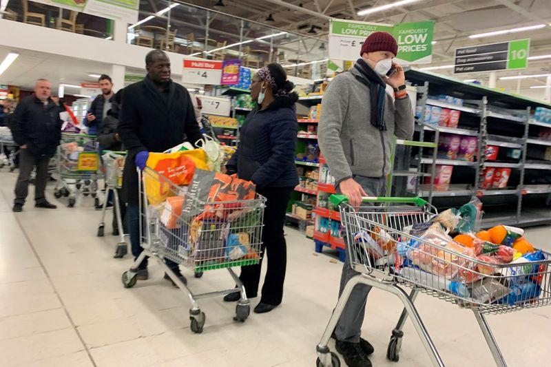 Shoppers walk past empty shelves inside a Tesco supermarket in Liverpool