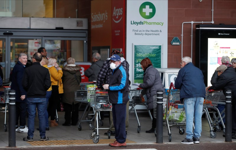 FILE PHOTO: People queue outside a supermarket during the spread of coronavirus disease