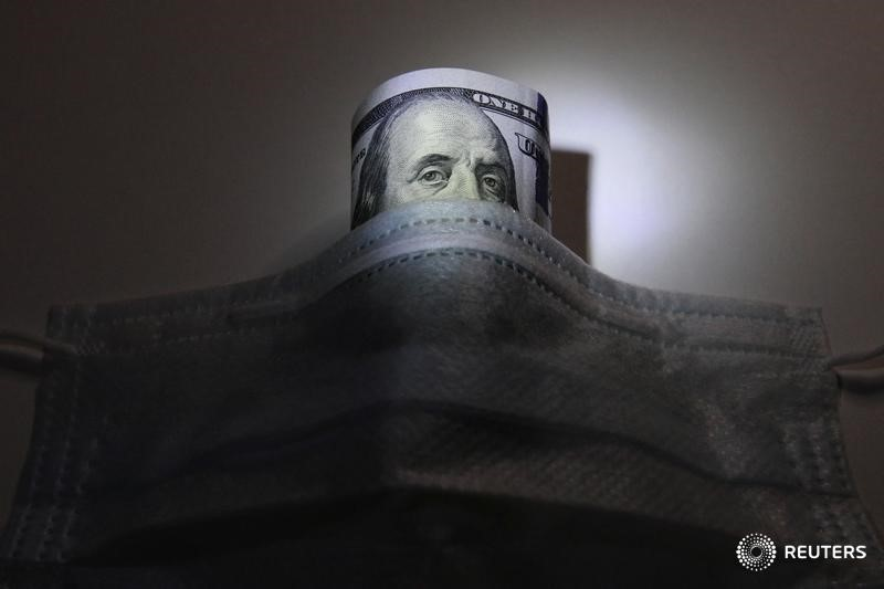 A U.S. dollar banknote is pictured behind a protective mask in this illustration