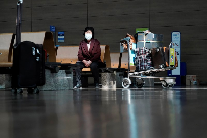 A woman wearing a mask to prevent contracting the coronavirus waits for her flight at Incheon