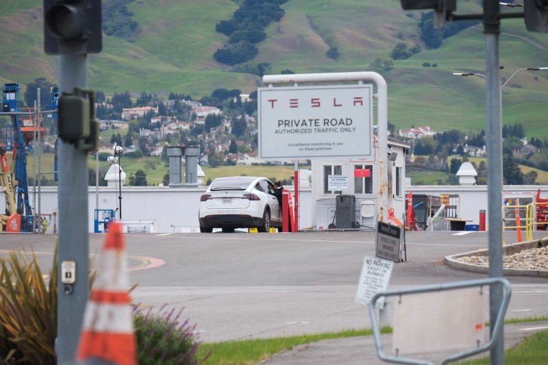 An employee of a Tesla Inc's U.S. vehicle factory is seen at a security gate in Fremont,
