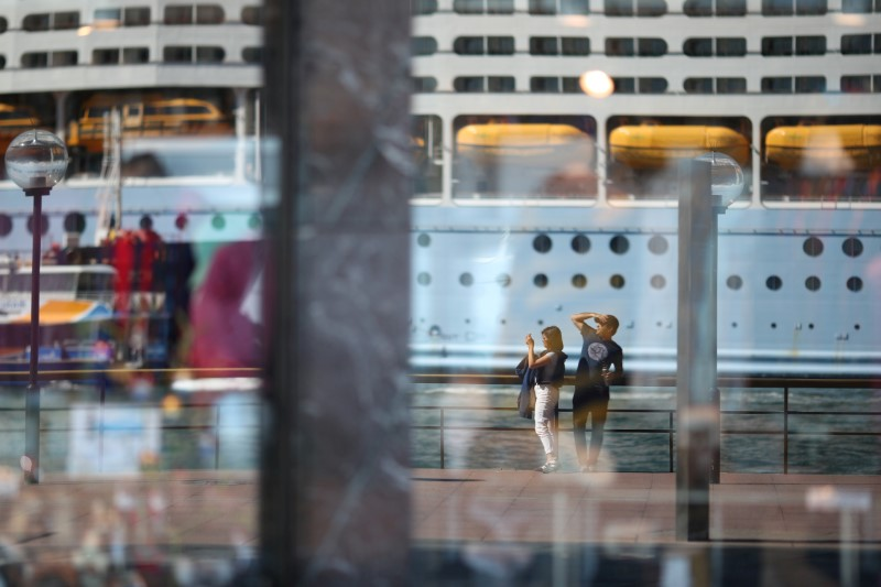 Two people, seen in the reflection of a shop window, stand on the mostly deserted waterfront of