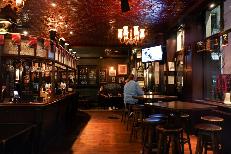 FILE PHOTO: People drink inside a quiet Irish pub in Soho, as the number of coronavirus