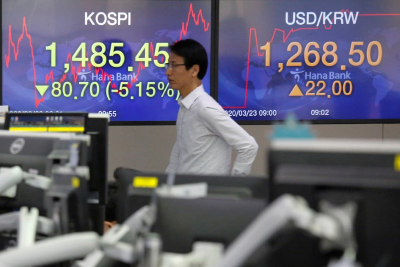 A currency dealer walks past in front of electronic boards showing the Korea Composite Stock