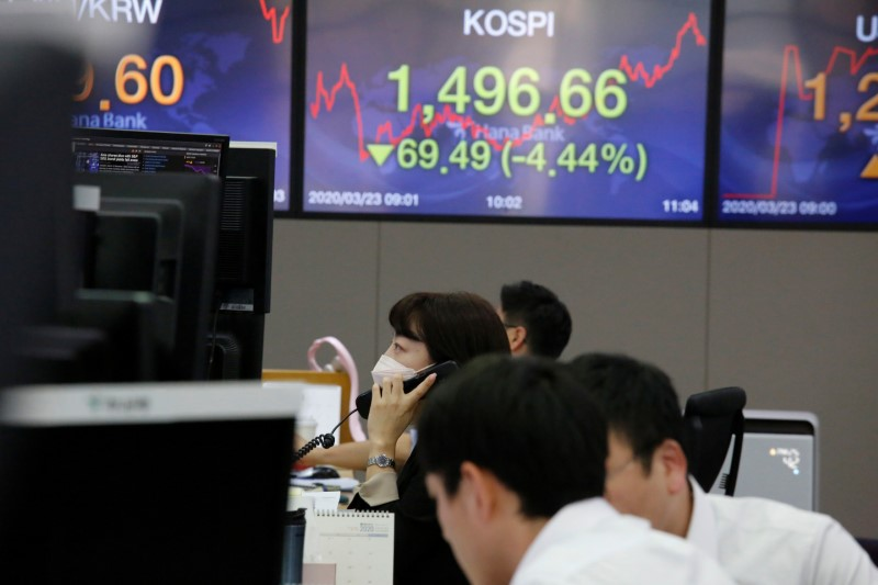A currency dealer talks on the phone in front of electronic boards showing the Korea Composite