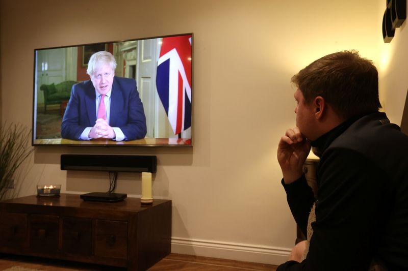 FILE PHOTO: A man watches British Prime Minister Boris Johnson's press conference as the spread