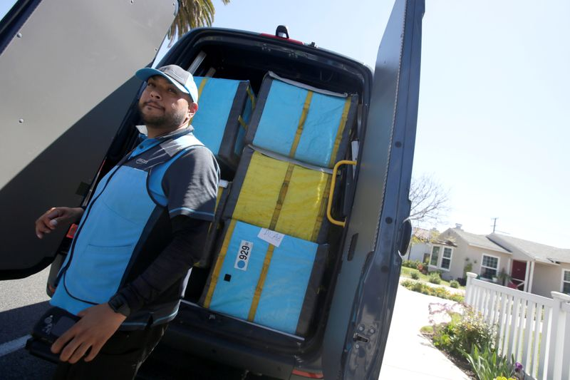 Joseph Alvarado picks up a package while making deliveries for Amazon during the outbreak of