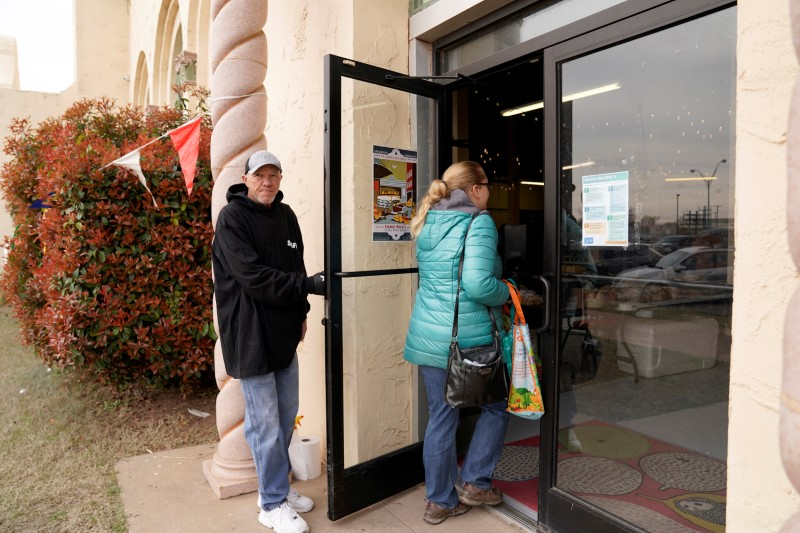 Chlebanowski looks for a customer's apartment to deliver produce in Norman