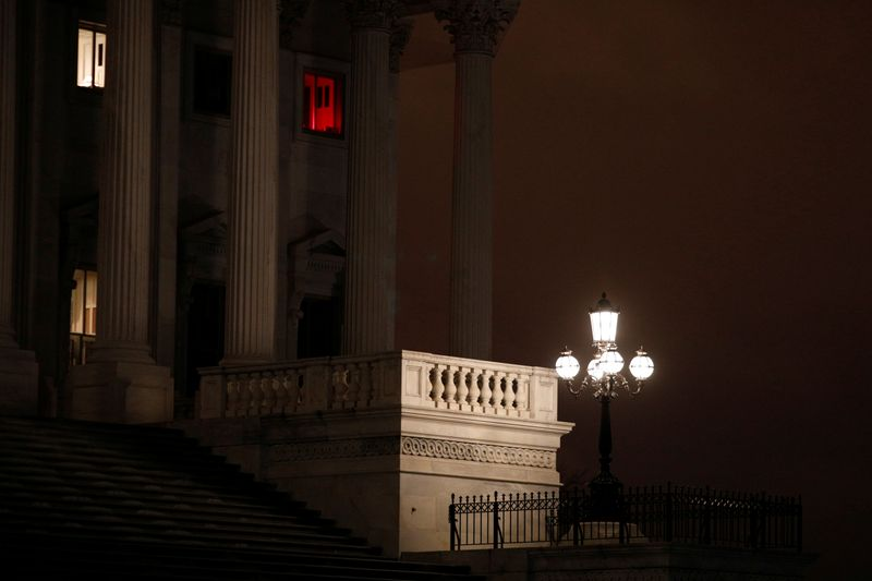 A window illuminated with a red light shines above the U.S. Senate steps, ahead of a vote on