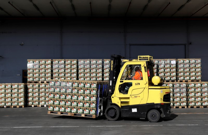 Workers walk past crates of beer on the yard of Plzensky Prazdroj brewery in Plzen