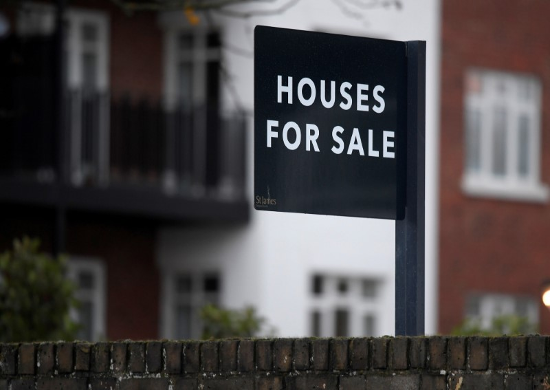 FILE PHOTO: Property sale signs are seen outside of a group of newly built houses in west