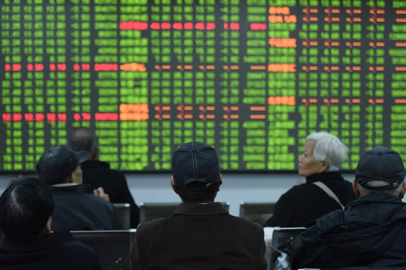 Investors sit in front of a board showing stock information at a brokerage house on the first