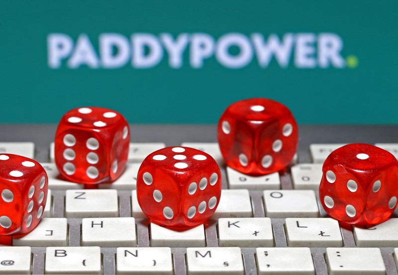 FILE PHOTO: Paddy Power logo is seen behind a keyboard and gambling dice in this illustration