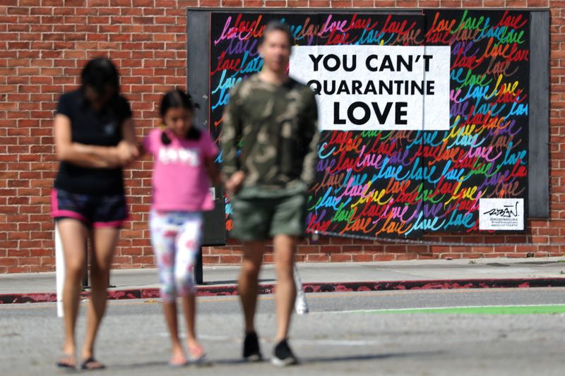 People walk in front of a mural, as the global outbreak of the coronavirus disease (COVID-19)
