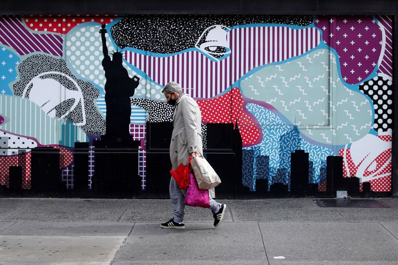 A man wears a protective face mask as he walks past closed stores in Manhattan during the
