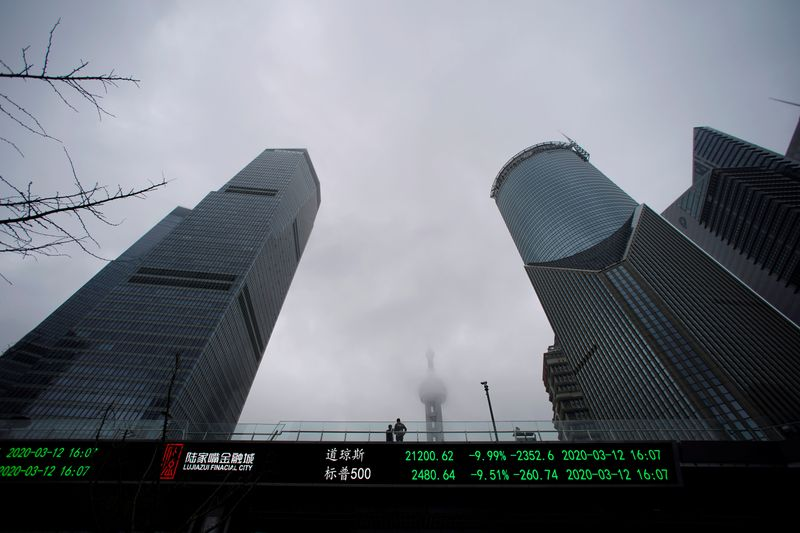People are seen on a pedestrian overpass with an electronic board showing the Dow Jones and S&P
