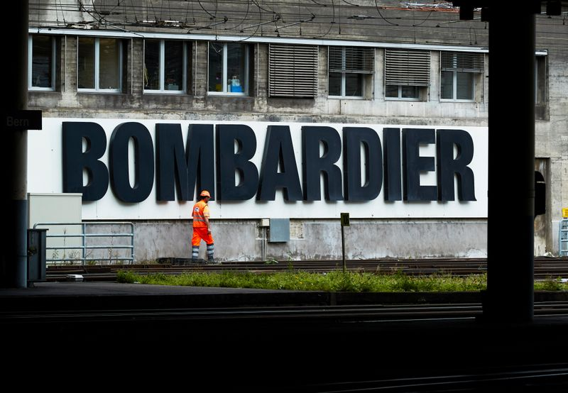 A worker walks in front of a Bombardier advertising board at the SBB CFF Swiss railway train