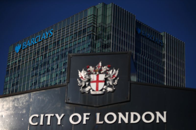 FILE PHOTO: Barclays' building in Canary Wharf is seen behind a City of London sign outside