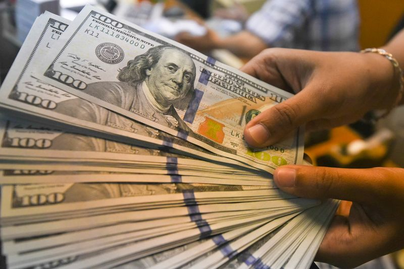 An employee shows U.S. dollars banknotes at a money changer in Jakarta