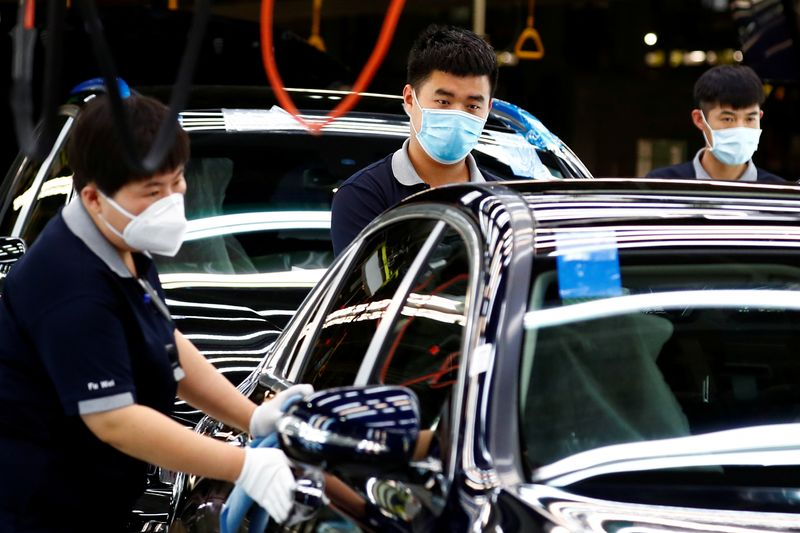 FILE PHOTO: Employees wearing face masks work at a plant of Daimler-BAIC joint venture's