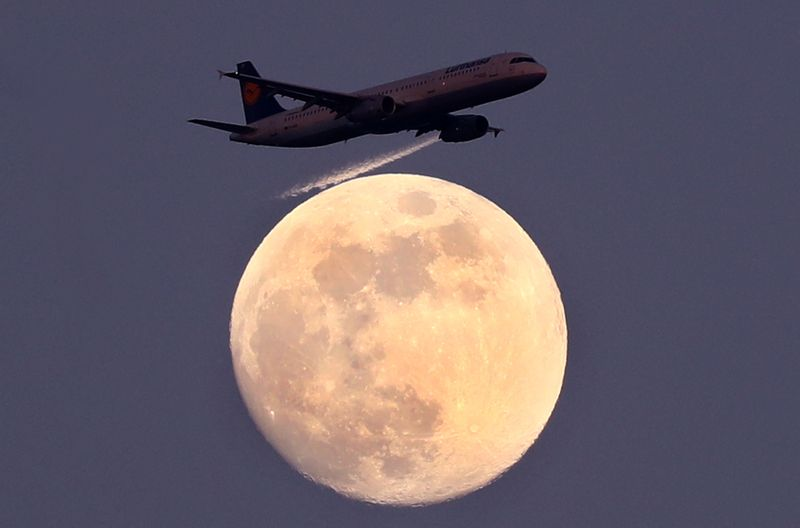 FILE PHOTO: An airplane of German air carrier Lufthansa passes the moon over Frankfurt