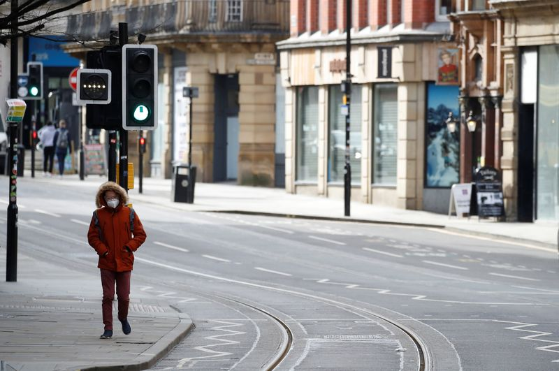 A man wears a mask as he walks along a deserted street amid the coronavirus outbreak in