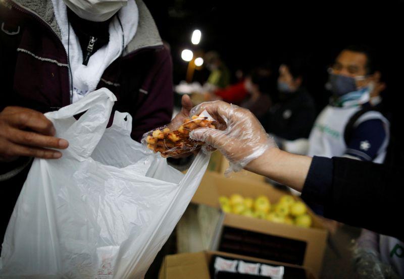 An elderly man receives food aid handouts, as the spread of the coronavirus disease (COVID-19)