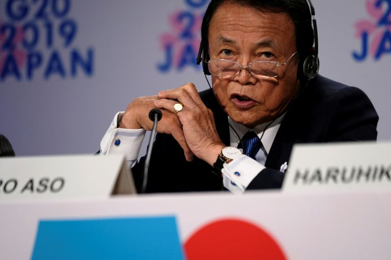 Japanese Finance Minister Taro Aso takes questions from reporters at the annual meetings of the