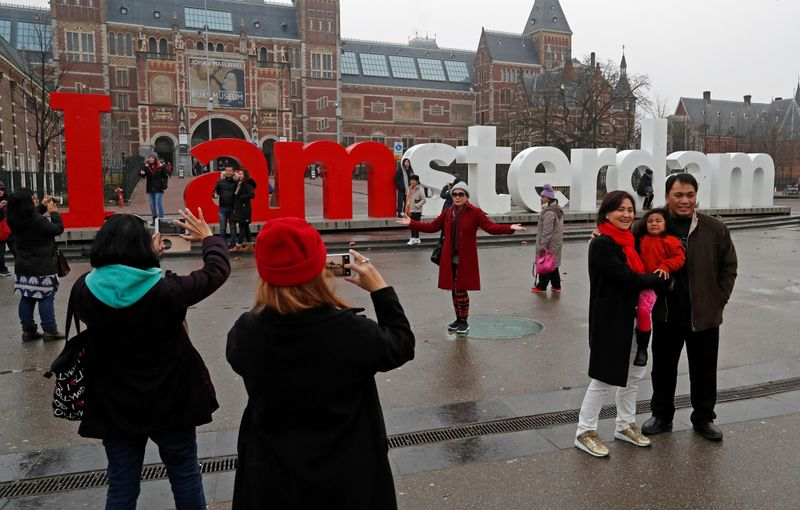 FILE PHOTO: Tourists pose for photos outside the Rijksmuseum in central Amsterdam