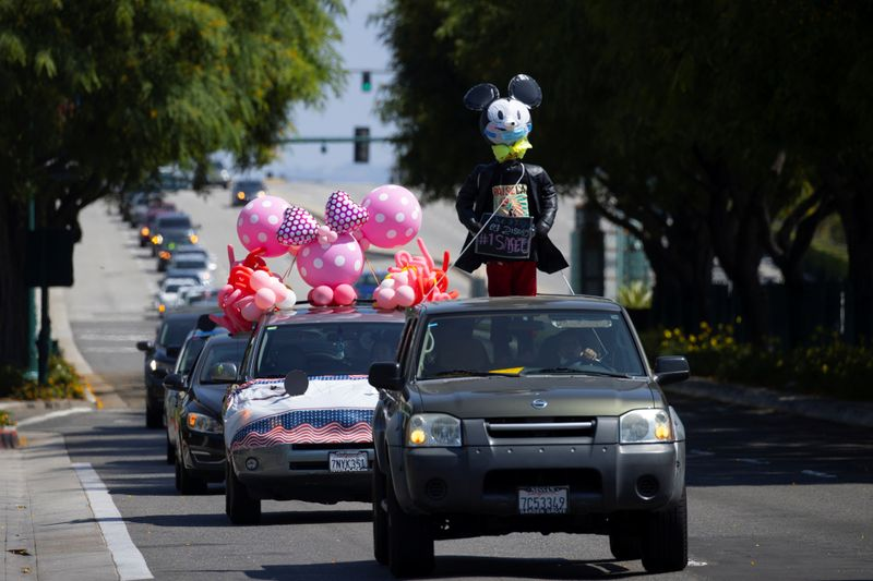 Disney cast members stage a car caravan outside Disneyland California, calling for higher
