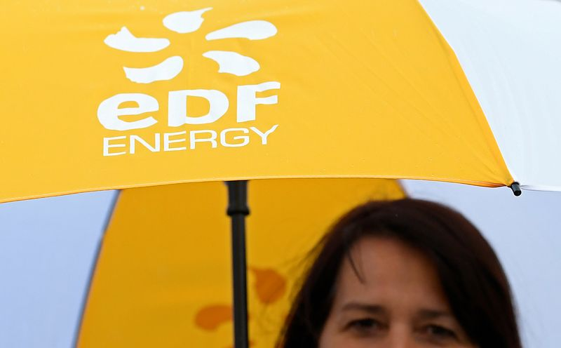 FILE PHOTO: An employee carries an umbrella with the EDF energy logo near the Hinkley Point C