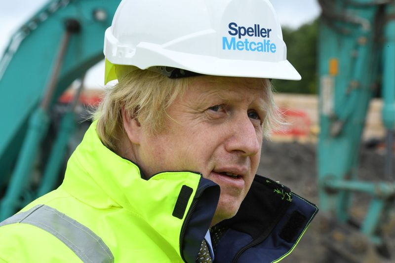 Britain's Prime Minister Boris Johnson speaks with workers as he visits the Speller Metcalfe's
