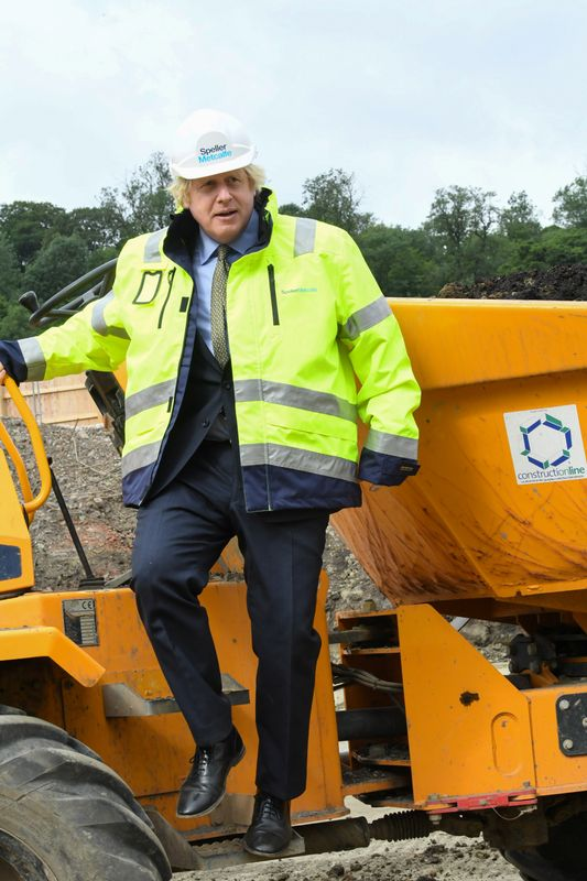 Britain's Prime Minister Boris Johnson gestures as he speaks with construction apprentices at