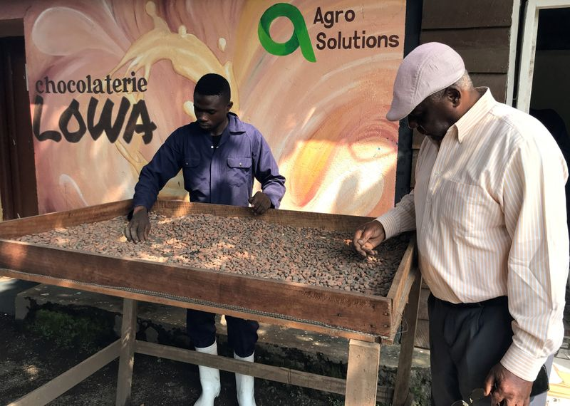 Lowa chocolate factory manager Kalinda Salumu Alexis and his employee dry cocoa pods at the
