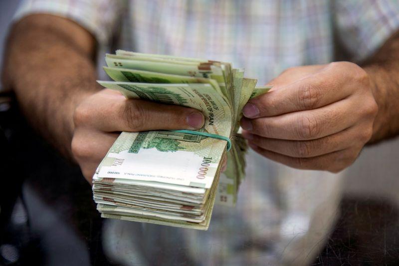 FILE PHOTO: A salesman counts money in Tajrish Bazaar, Tehran