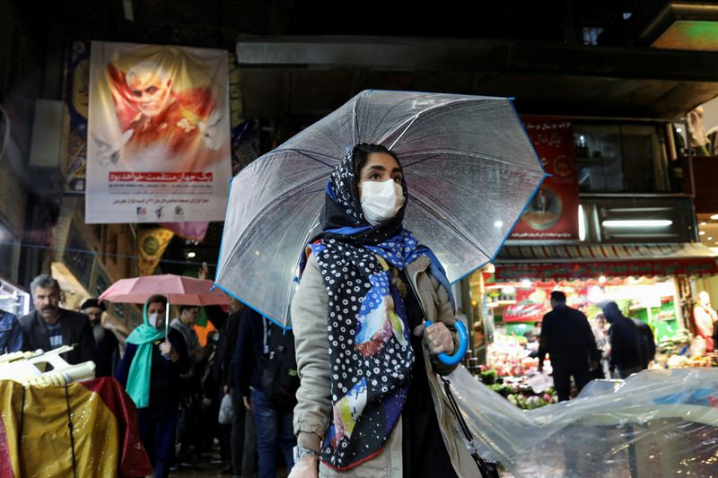 FILE PHOTO: Men wear protective face masks and gloves, following the outbreak of coronavirus,