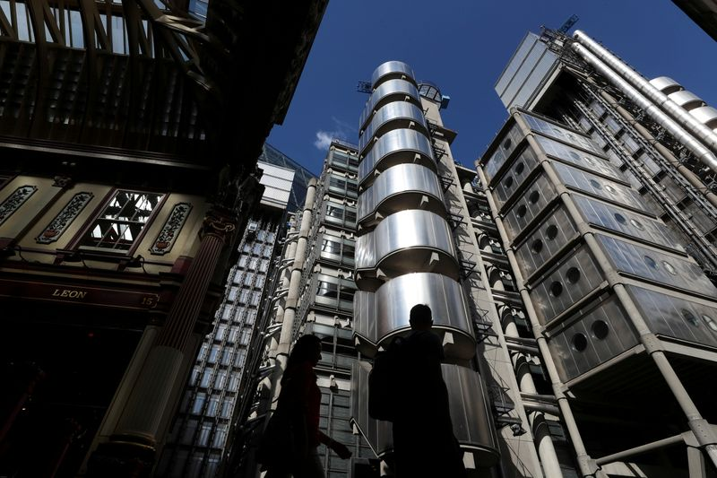FILE PHOTO: People walk outside Lloyds of London's headquarters in the City of London