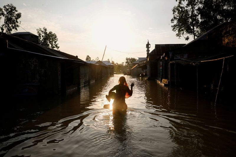 FILE PHOTO: A woman is silhouetted when she walks on a flooded road in Jamalpur
