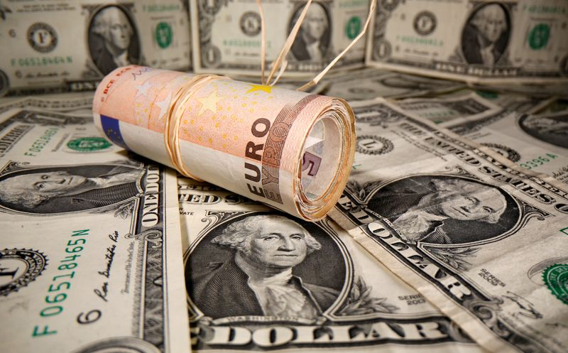 Rolled Euro banknotes are placed on U.S. Dollar banknotes