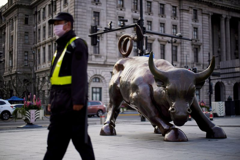 FILE PHOTO: Security guard wearing a face mask walks past the Bund Financial Bull statue on The