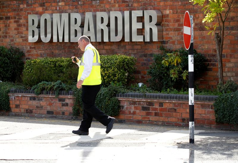 FILE PHOTO: A worker walks past the entrance to the Bombardier plant in Derby