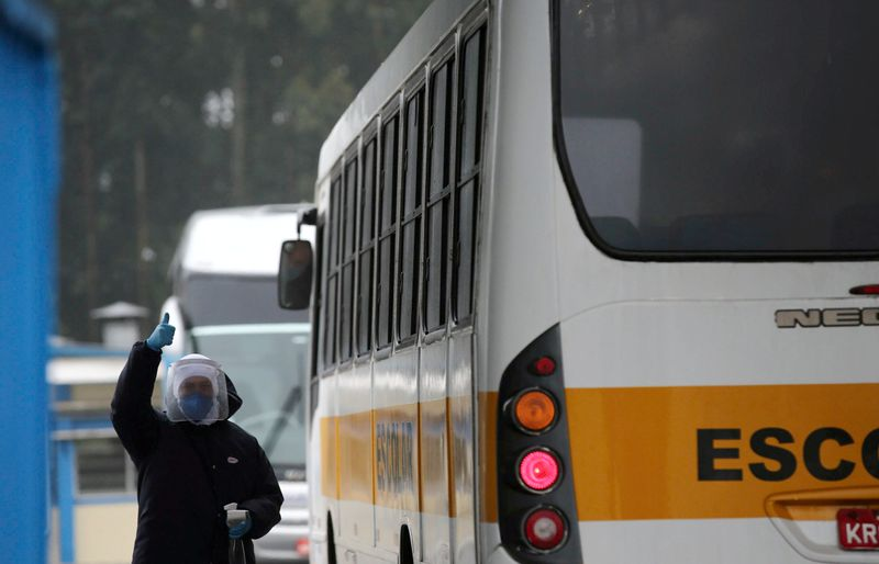 A JBS SA poultry factory employee checks a bus driver's temperature after the company was hit